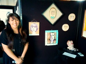 Nativity graduate Anat Dupo ('10) poses next to her senior-year exhibition of artwork at the School for the Creative and Performing Arts on May 3, 2014